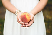 Peach in the hands of a woman