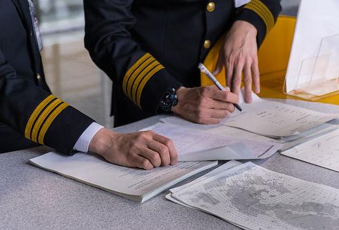 Airline pilot reading flight document be