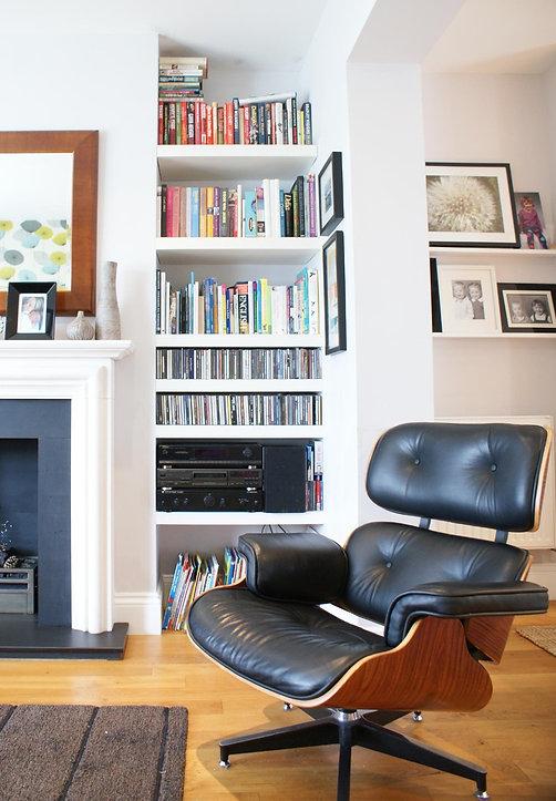 bespoke shelving, limestone fireplace and eames chair