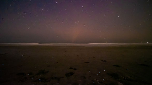 Footbridge beach where stars mirror bioluminecent plankton across the waves taken by Jasper Lior