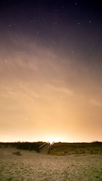 Nighttime night sky at Footbridge beach with stars and purple colorful clouds