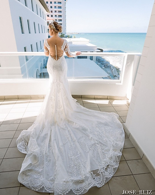Puerto Rican bride in a luxurious lace gown dress near the beach
