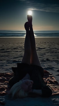A beautiful woman holding the moon up with her legs and laying on a beach taken by Jasper Lior