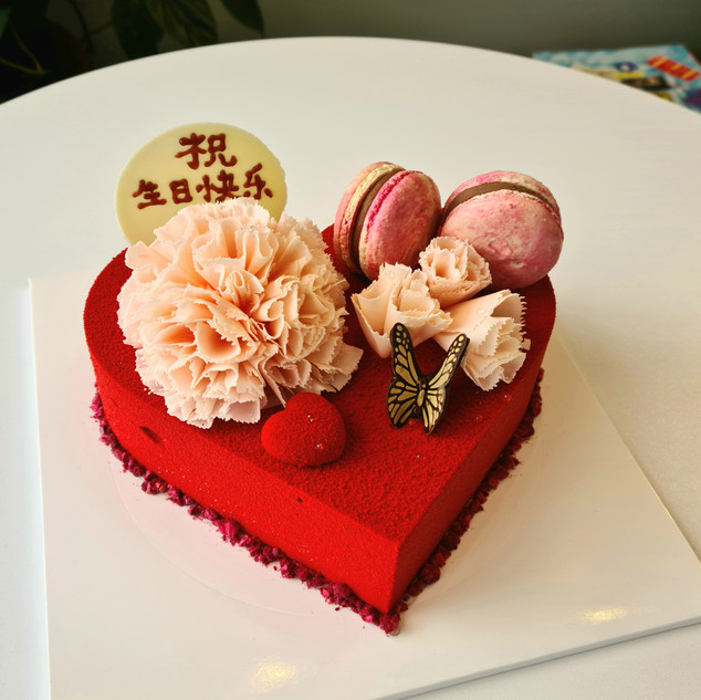 Heart shaped cake with macarons and flowers