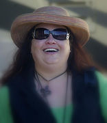 Anne Mary, smiling in hat & sunglasses