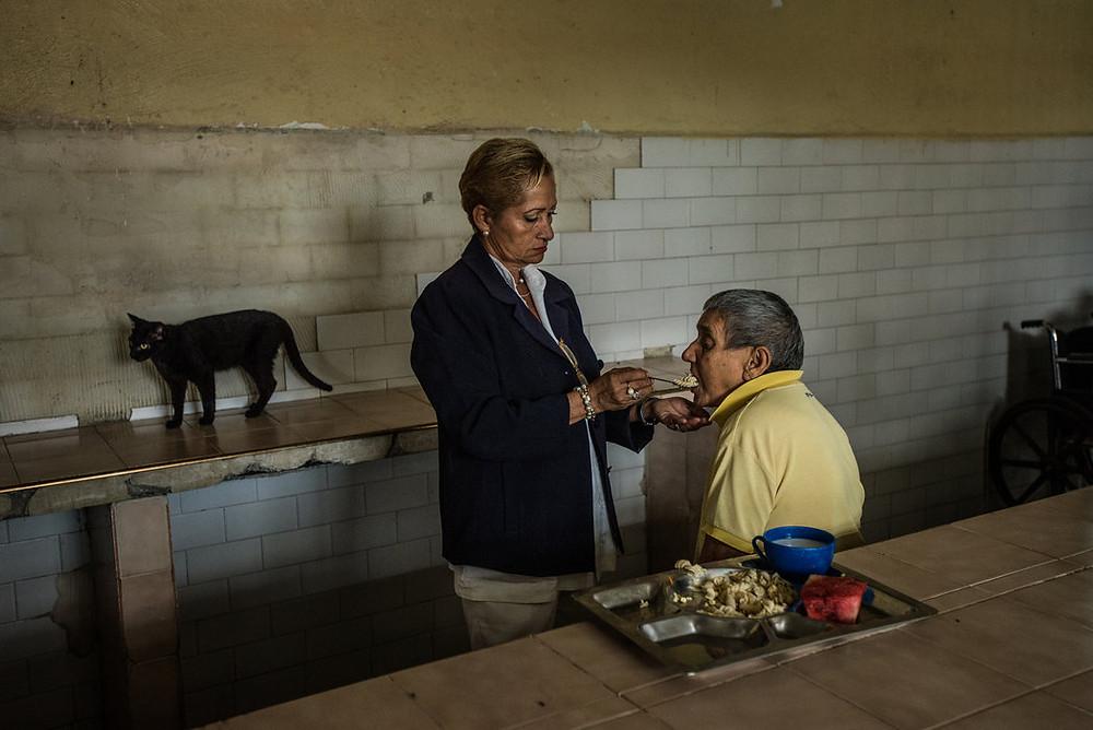 Szefowa pielęgniarek, Évila García, karmi ślepego pacjenta. Nie ma warunków sanitarnych w szpitalu i w obiekcie są bezpańskie koty i psy, brudne, zapchlone. Meridith Kohut dla The New York Times