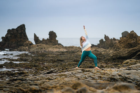 woman on beach in a yoga pose, reverse warrior pose, mindfulness coach
