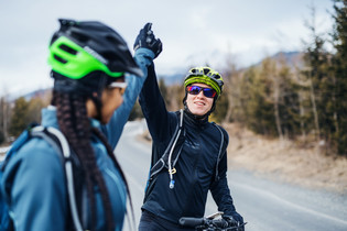 two-mountain-bikers-standing-on-road-out