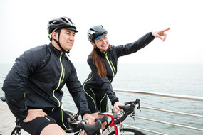 happy-woman-cyclist-showing-finger-on-so