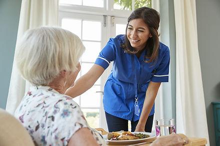 care-nurse-serving-dinner-to-a-senior-wo