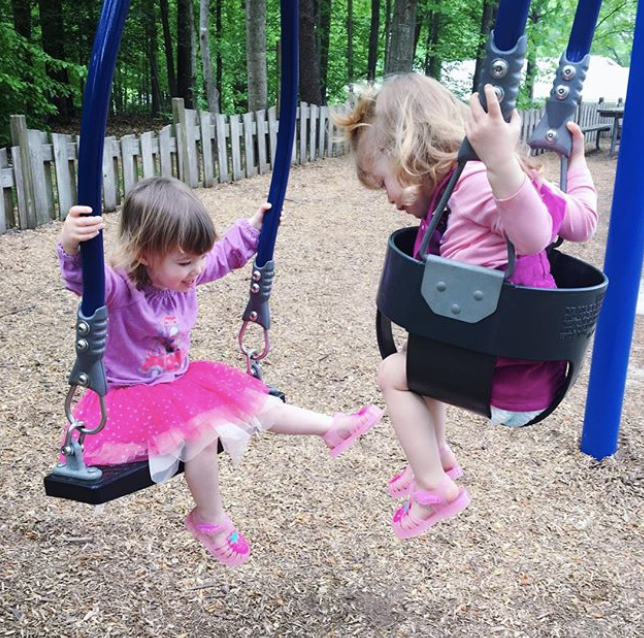 twin toddlers in a double swing