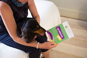 Jane looking at info folder with dog on lap.jpg
