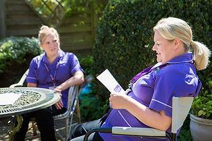 2 HCA's in garden looking at brochure.jpg