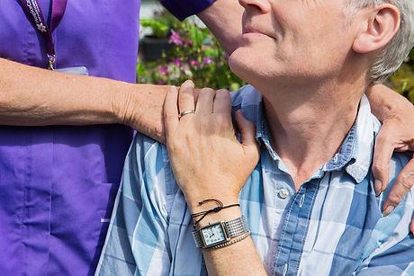 Client looking up to HCA with hand on shoulder in garden.jpg