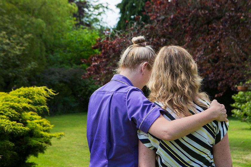 Nurse with arm around client in garden.jpg