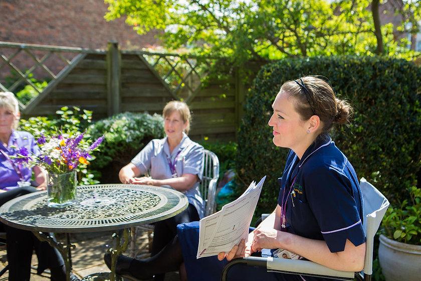 Carrie having meeting with HCA's in garden.jpg