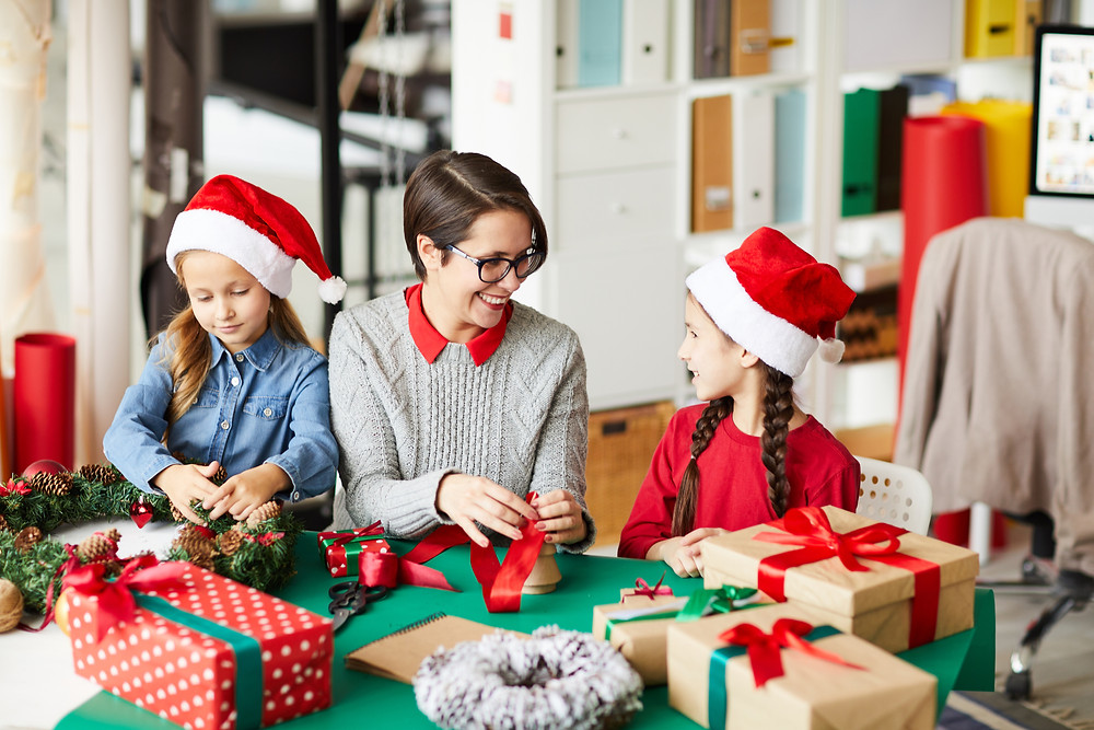 Women with glasses smiles at two young girls in Santa hats as they wrap presents