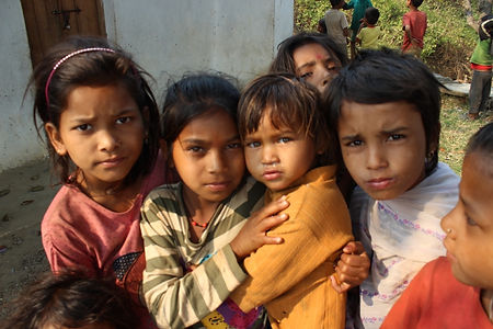 7 Nepali children looking at camera. Adolescent girl in middle is holding a younger child close.