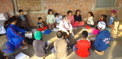 Group of Nepali children sitting on floor in a circle. Children have books around them. Older woman sitting in middle of the circle smiling.