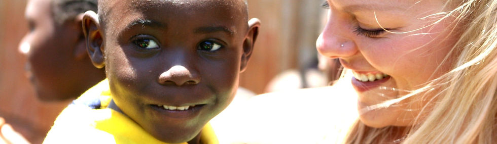 Volunteer holding a young boy from the Kawangware Children's Centre in Nairobi. Both are smiling.