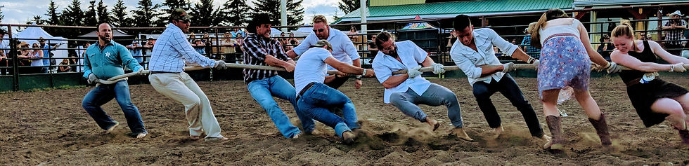 Group of people in Western wear pulling hard on a rope together while playing game of Tug-of-War