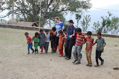 Two adult women playing a game in a field with group of Nepali children. They are smiling while holding hands and walking in a line.