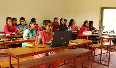 Young Nepali women from the Karuna Girls College in Lumbini, Nepal on computers at desks. They are dressed in colorful saris.