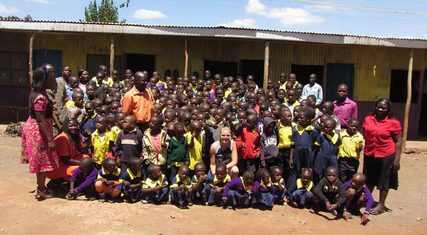 Large group of students and teachers gathered together at the Kawangware Children's Centre in Nairobi, Kenya. They are in front of the school.