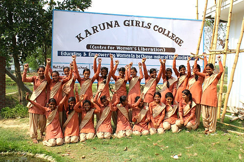 """Karuna Girls College students laughing with arms up in celebration. They are wearing their uniforms, in front of sign saying """"Karuna Girls College, Centre for Women's Liberation. Educating & Empowering Women to be Change-Makers of their Society"""""""