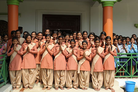 """Nepali girls from Karuna Girls College smiling and wearing school uniforms. They have their palms pressed together in the """"Namaste"""" gesture."""
