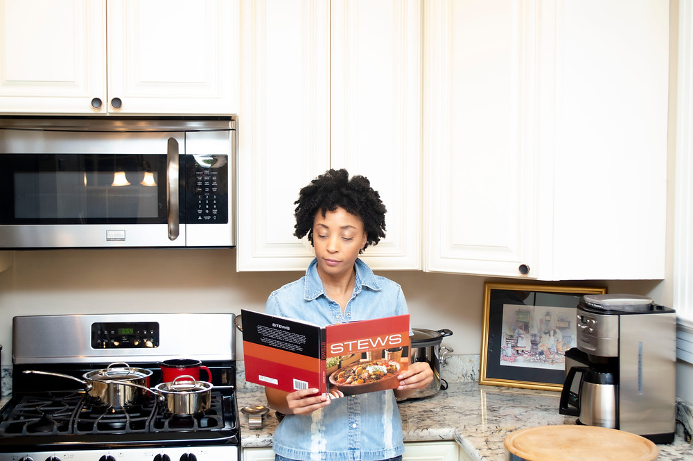 Woman looking through a cookbook for a recipe.