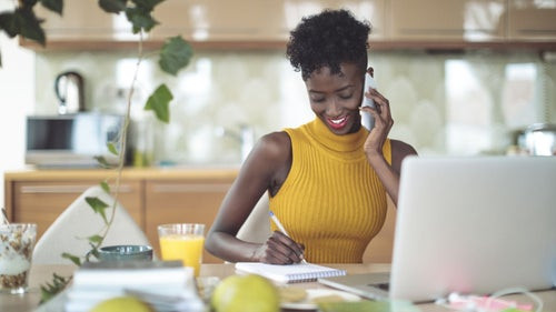 Black woman at her desk working.