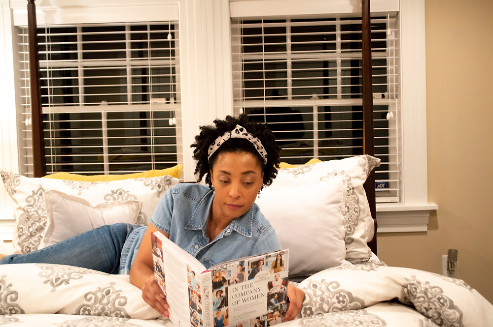Woman lying on a bed at night reading.
