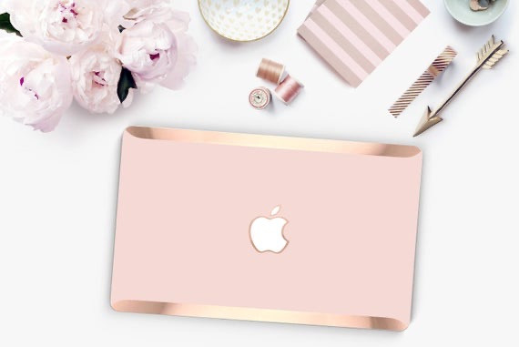 Rose gold and light pink laptop with flowers and other stationary.