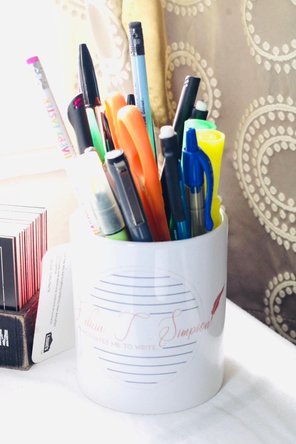 white coffee mug with pens and pencils in it