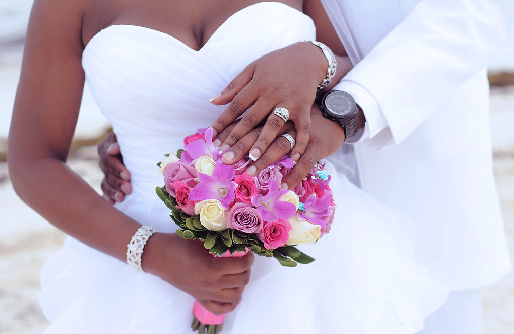Black married couple hands and bouquet
