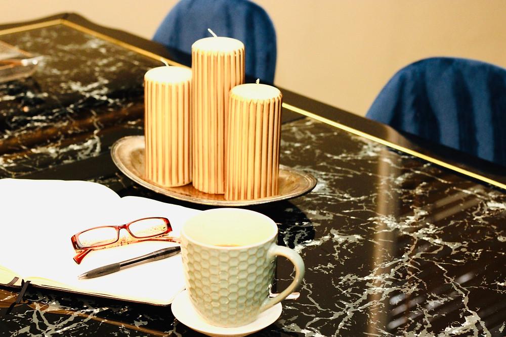 Coffee mug, planner, glasses and pen.