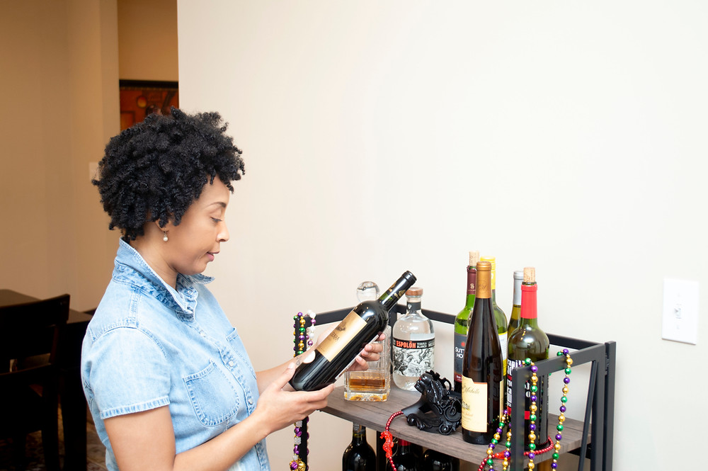 A woman selecting a bottle of wine to drink.
