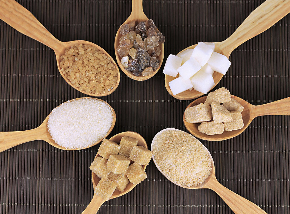 Image of various sugars in wooden spoons