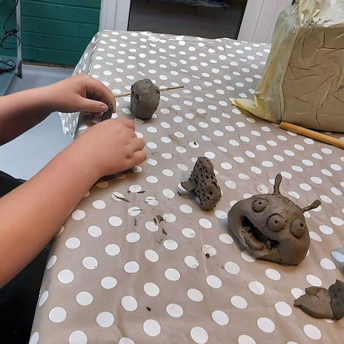 A boy's hands are seen forming a clay pinch pot monster