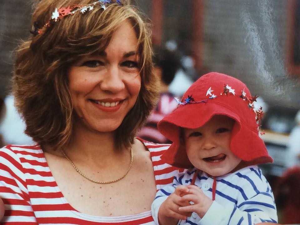 A beautiful mother holds her baby son at a Fourth of July celebration