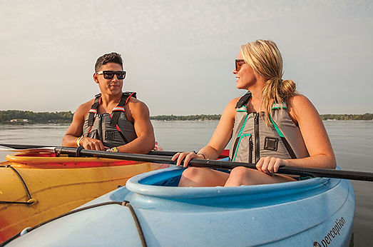 Male and female wearing Onyx paddle life jacket, kayaking on a lake
