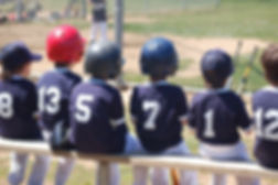 kids baseball team sitting on bench