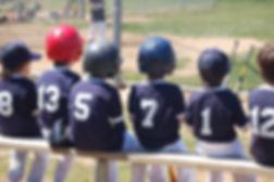 kids baseball team sitting on bench