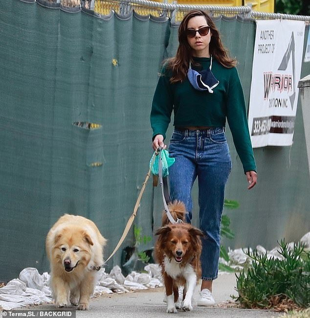 Actress Aubrey Plaza walking her two dogs while using Seafoam Poopy Packs from Metro Paws