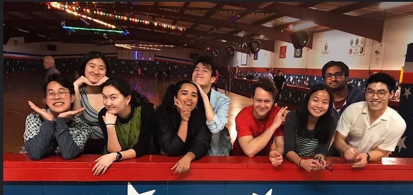 Nine students pose together in a roller skating rink