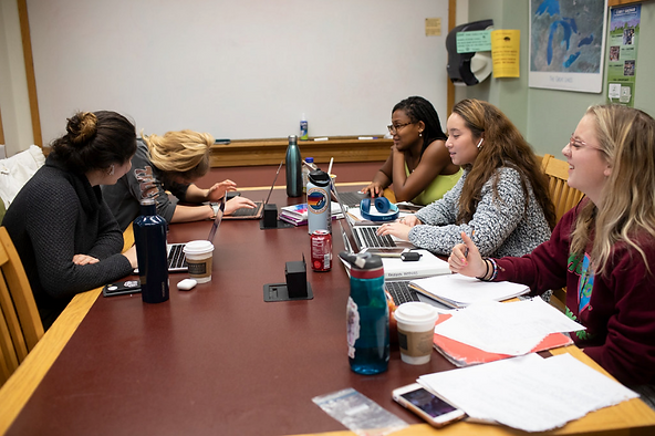 Five students study together at a table in a library study room