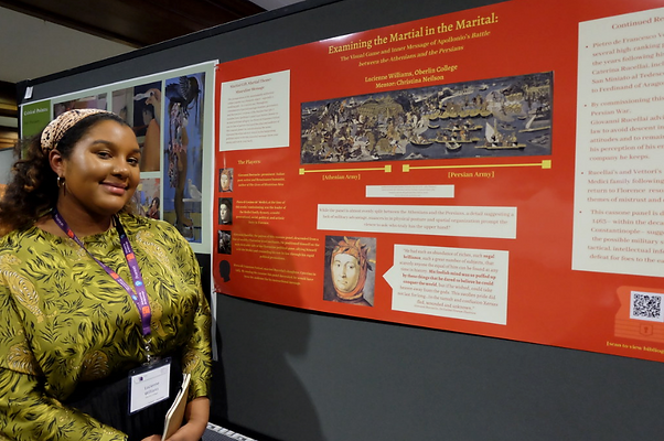 A student stands in front of a poster presentation