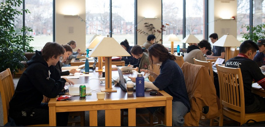 Students sit studying quietly at tables in a science library, with large windows in the background