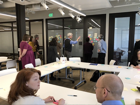 A group of men and women work together to arrange colored sticky notes on a glass window in a conference room.